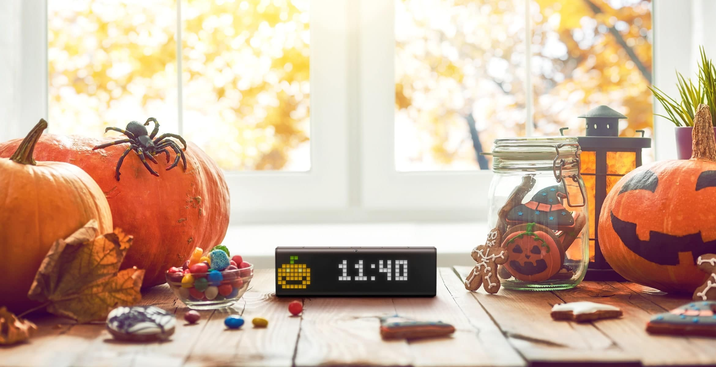 LaMetric Time smart clock displays time and a pumpkin clock face, standing on a table with Halloween decorations